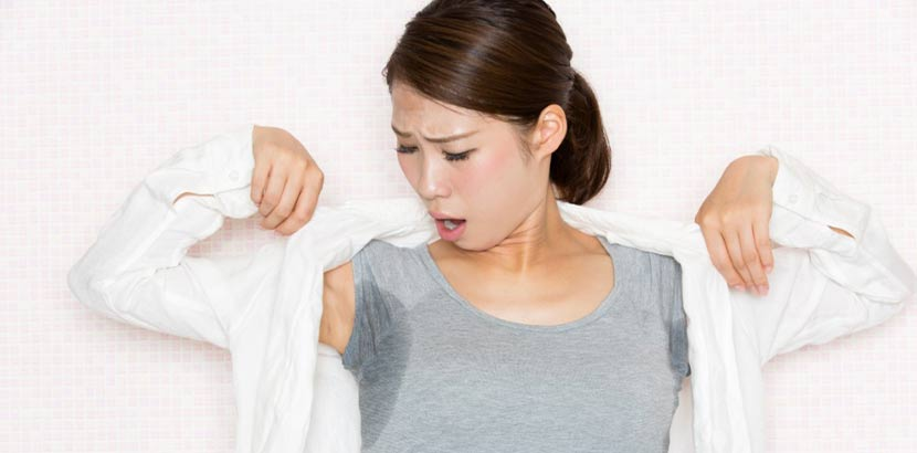 Junge asiatische Frau mit offener weißer Bluse und grauem T-Shirt, auf dem sich unter den Achseln durch starkes Schwitzen sehr große Schweißränder abzeichnen.