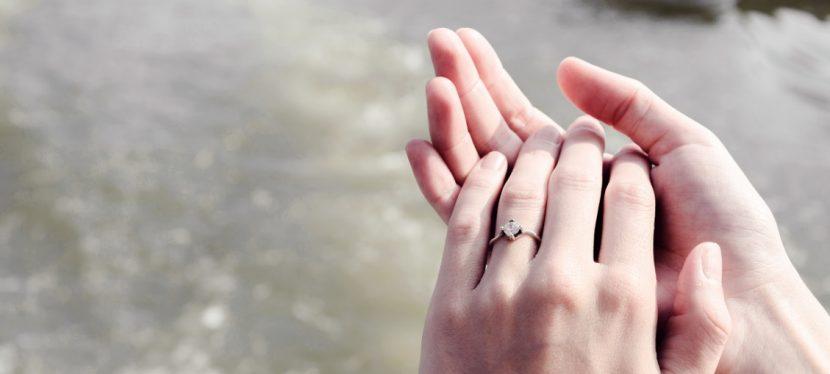 Damenhände mit einem Edelsteinring, der im Rahmen einer Diamantbestattung entstanden ist. Diamant aus Asche.