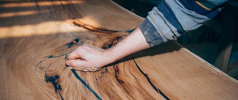 Mit Epoxidharz Holz versiegeln: Ein Mann streicht mit der Hand über einen polierten Epoxidharz Tisch