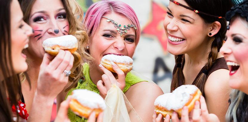 Gruppe von Frauen im Fasching, die Krapfen essen und sich freuen. Fasching 2020.