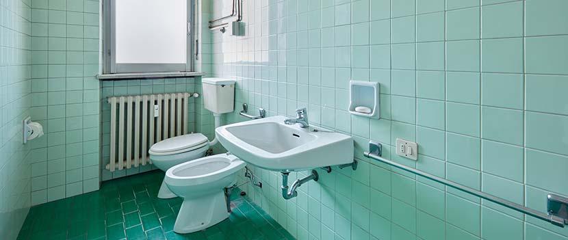 Fliesen streichen: Ein Badezimmer mit grünen Wandfliesen und Bodenfliesen.