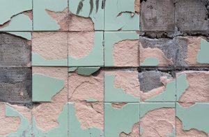 Abgeplatzte Fliesen reparieren und Risse ausbessern: Bei den Fliesen auf dem Foto ist das bereits zu spät. Die grünen Fliesen sind bereits zu stark von der Wand abgeplatzt.