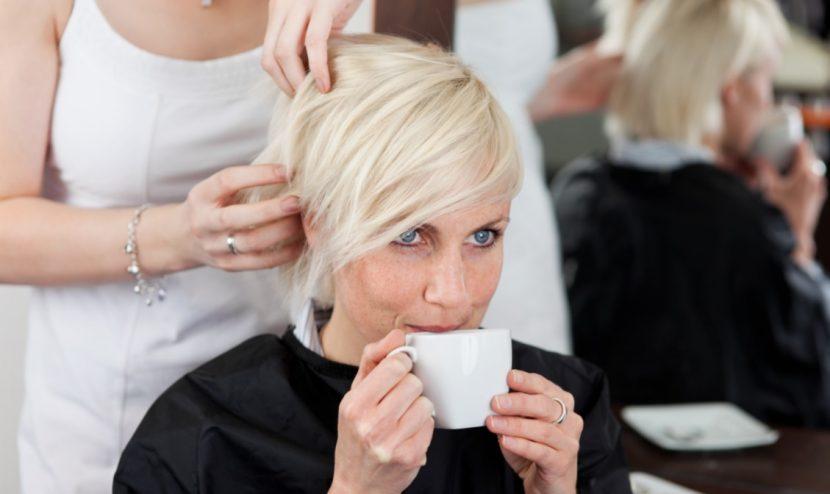 Junge blonde Frau, die beim Friseur Graz entspannt einen Kaffee trinkt, während sie eine neue Frisur bekommt.