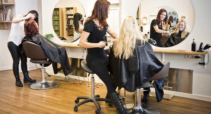 Blonde Kundin beim Friseur Wien im Beauty Salon, wird von einer hübschen brünetten Friseurin bedient.