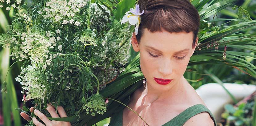 Trendfrisuren 2021: Eine Frau mit einem Pixie Cut und kurzen Stirnfransen trägt einen grünen Blumenstrauß.