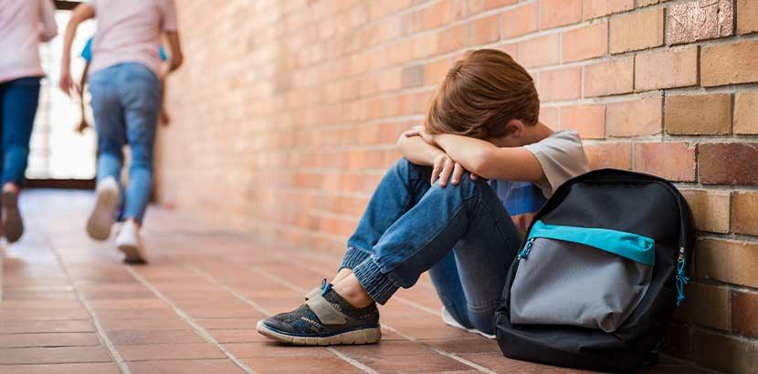 Kleiner Junge, der in seiner Schule traurig am Boden sitzt, weil er wegen seiner Legasthenie gehänselt wurde.