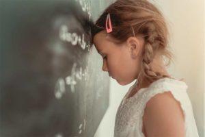 Blondes Mädchen, das aufgrund seiner Legasthenie LRS Rechtschreibschwäche Probleme in der Schule hat.