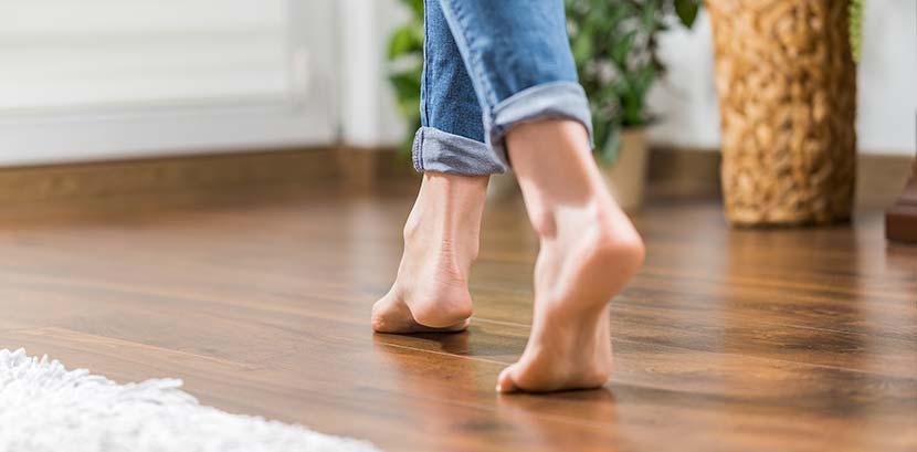 Parkettlack auf Wasserbasis: Eine Frau läuft barfuß über einen Parkettboden. Man sieht nur ihre Beine, sie trägt eine Jeans.