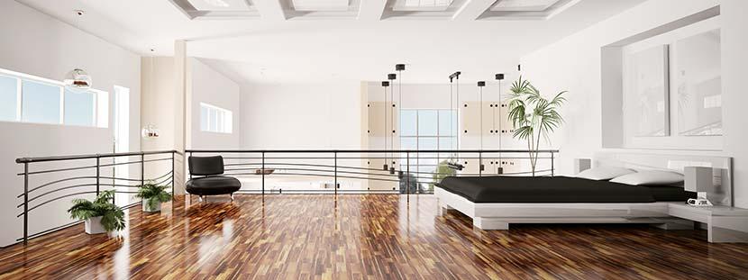 Ein modernes Loft mit Bett, Schreibtischsstuhl und weißen Wänden. Der braune Parkettboden wurde mit glänzendem Parkettlack behandelt.