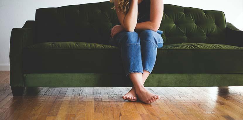 Parkettlack auftragen: Eine Frau sitzt auf einem grünen Sofa. Sie ist barfuß und stellt ihre Füße auf den Parkettboden.