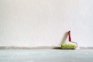 Hier wird Rollputz innen aufgetragen: Eine Farbrolle lehnt an der weißen Wand.