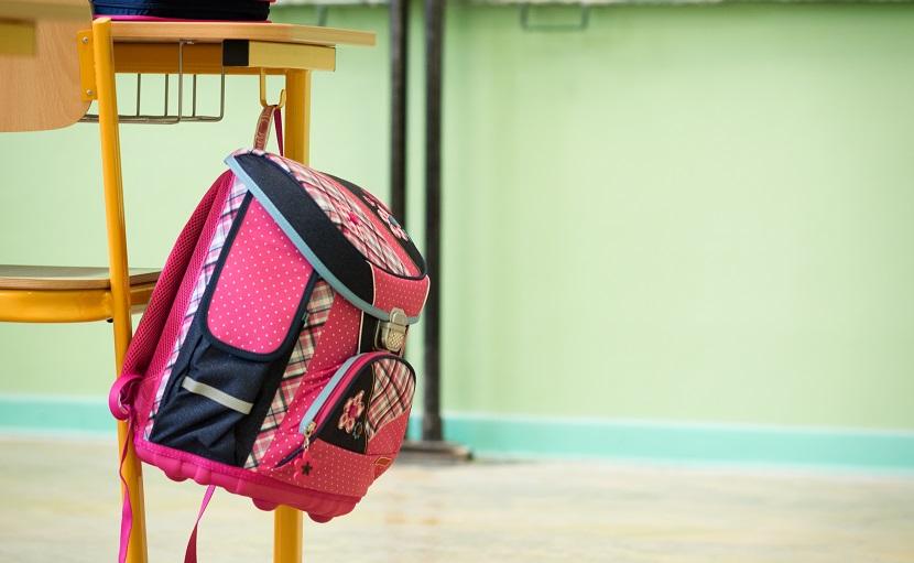 Rosa Schultasche hängt an Haken beim Tisch