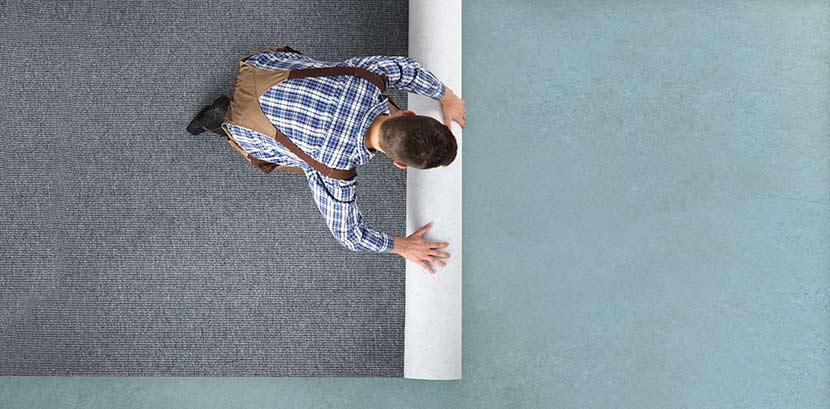 Teppich verlegen: Ein Mann rollt einen Teppichboden aus.