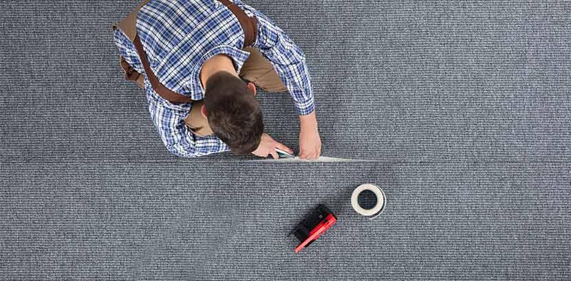 Teppich verlegen: Ein Mann schneidet den Teppichboden zurecht.