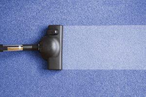 Staubsauger reinigt blauen Teppich