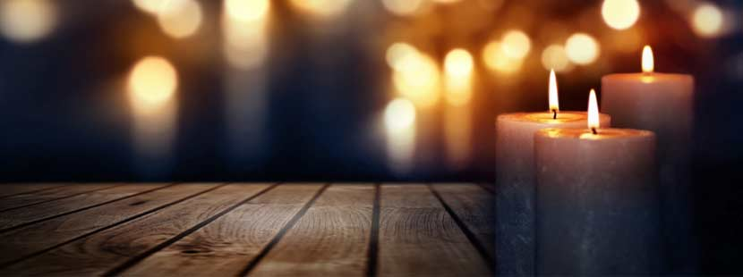 Drei brennende Kerzen auf einem Holztisch vor dunklem Hintergrund, in dem noch mehr Lichter leuchten. Trauerfall Checkliste Österreich.