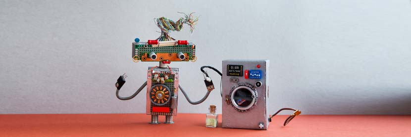 Waschmaschine stinkt: Ein kleiner Roboter neben einer Spielzeugwaschmaschine.
