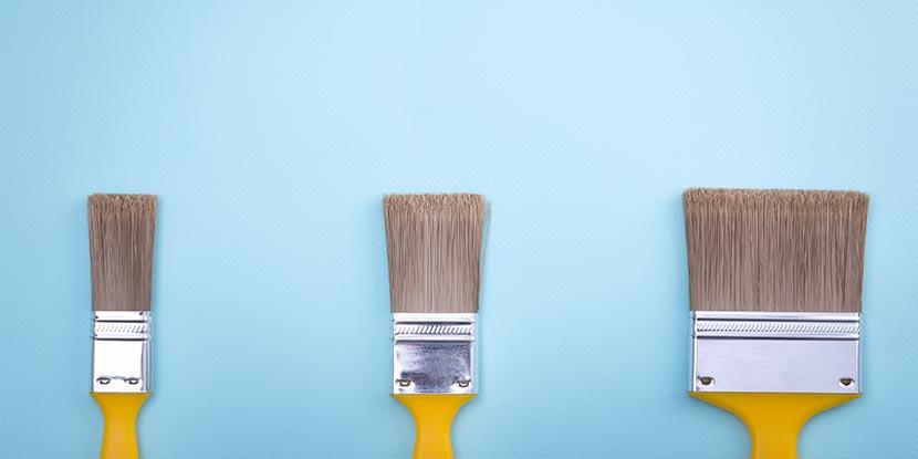 Wohnung streichen: Drei verschieden große Pinsel liegen auf einem blauen Untergrund.
