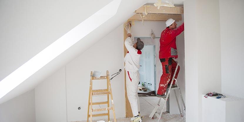 Wohnung streichen: Professionelle Maler streichen eine Wohnung mit Dachschräge.