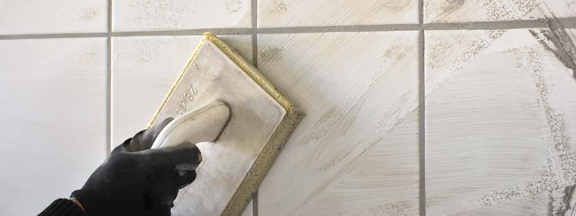 Zementschleier entfernen: Eine Person verfugt helle Fliesen an der Wand. Dabei bleibt grauer Zementschleier zurück.