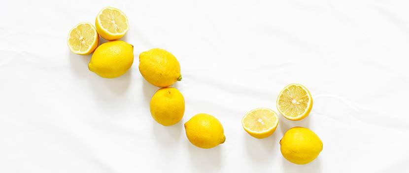 Zementschleier entfernen: Eine Handvoll ganze und aufgeschnittene Zitronen auf einem weißen Tuch.