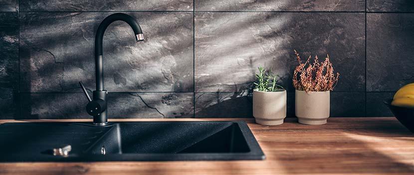 Zementschleier entfernen: Eine moderne Küche mit Natursteinfliesen aus Schiefer und einer Ablagefläche aus rötlichem Holz.