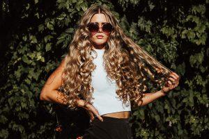 Dauerwelle: Eine hübsche junge Frau mit Sonnenbrille und großen Locken.