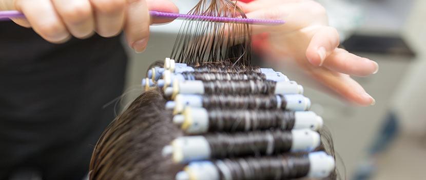 Eine Friseurin setzt eine Dauerwelle.