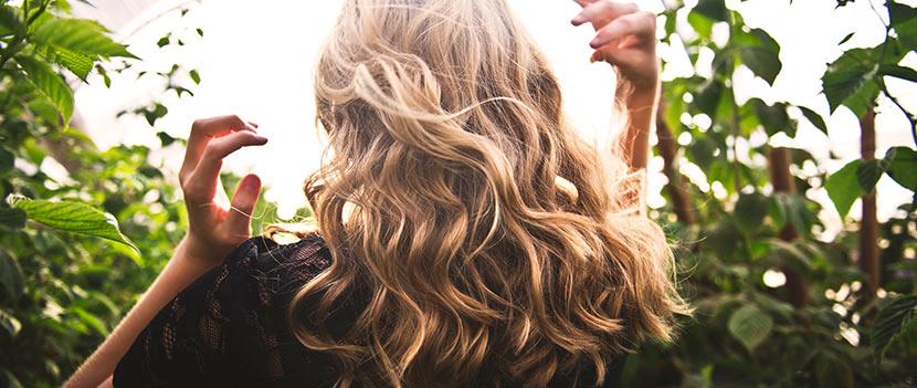 Dauerwelle lange Haare: Eine Frau mit gelocktem, blonden Haar dreht der Kamera den Rücken zu und steht in der Natur.