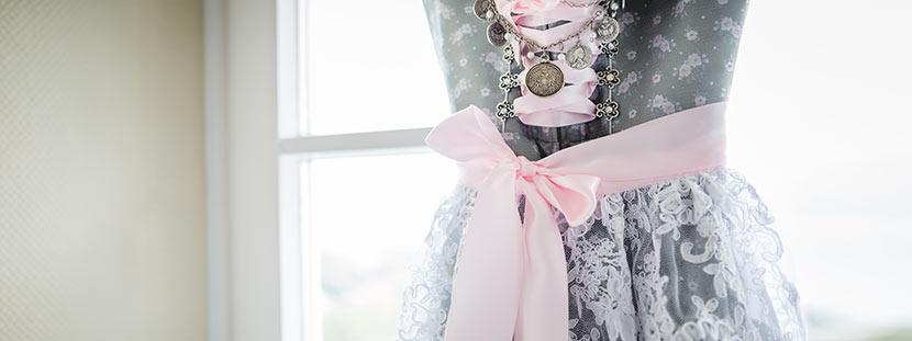 Ein hellgraues Dirndl mit rosa Dirndl Schleife, das im Fenster hängt.