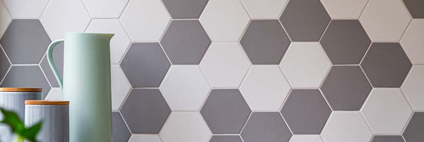 Fiesen auf Fliesen kleben: Eine Küche mit neuen, sechseckigen Fliesen in Grau und Weiß.