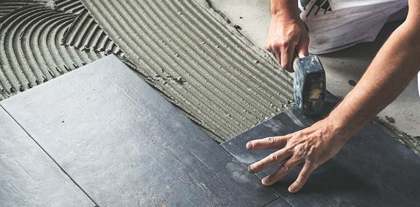 Fliesen auf Fliesen kleben: Ein Mann klopft schwarze Bodenfliesen mit einem Gummihammer fest.