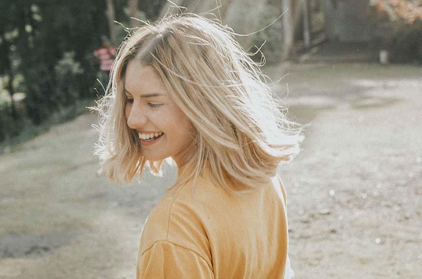 Frisurentrends 2019: Eine junge Frau mit blondem, schulterlangem Haar steht in einem sonnigen Garten und lächelt. Sie trägt ein gelbes Shirt.