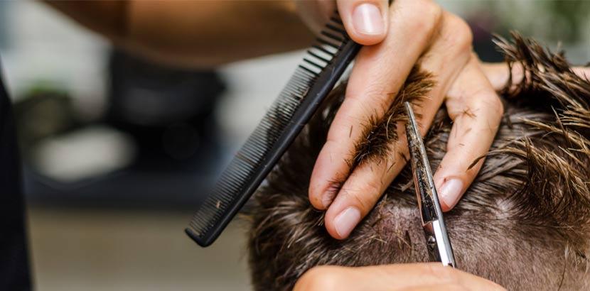 Close up von Friseurhänden, die die Haare eines jungen Mannes in Vorbereitung auf eine Haartransplantation schneiden.