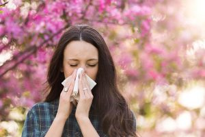 Frau putzt sich die Nase wegen Pollenallergie