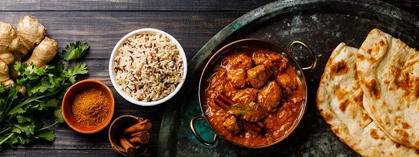 Indische Restaurants Wien: Ein Tisch, auf dem Reis, Curry, ein Eintopf, Naan-Brot, Koriander und Ingwer stehen.