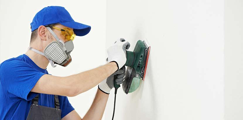 Ein Mann entfernt Latexfarbe von der Wand und nutzt dazu eine Schleifmaschine. Er trägt eine Atemschutzmaske.