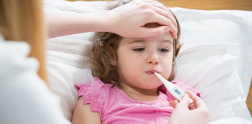 Ein Kind liegt mit Fieber durch Masern im Bett. Eine Frau misst mit einem Fieberthermometer die Temperatur des Kindes.