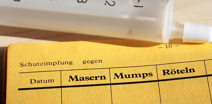 Ein Impfbass für Mumps, Masern und Röteln. Daneben liegt eine Spritze.