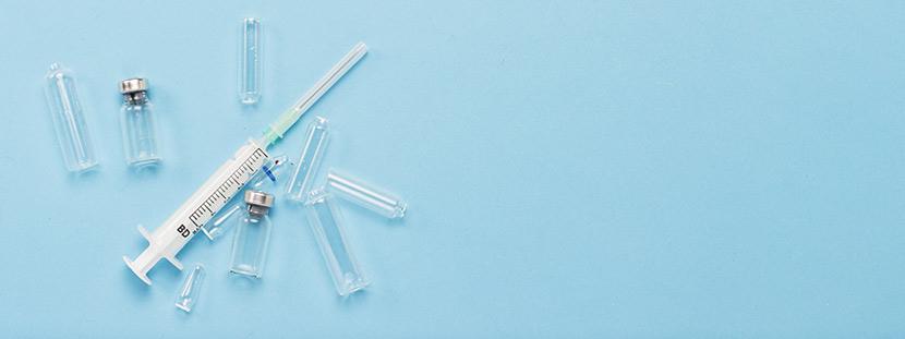 Eine Spritze und verschiedene Kanülen, mit der die Masern Impfung durchgeführt wird, auf einem blauen Untergrund.