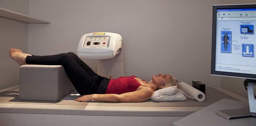 Ältere Frau bei der Osteoporose Therapie, bei der gerade eine Knochendichtemessung durchgeführt wird.