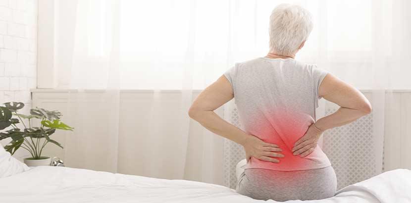 Ältere Frau, die mit Rückenschmerzen auf ihrem Bett sitzt und sich den Rücken hält. Osteoporose Therapie.