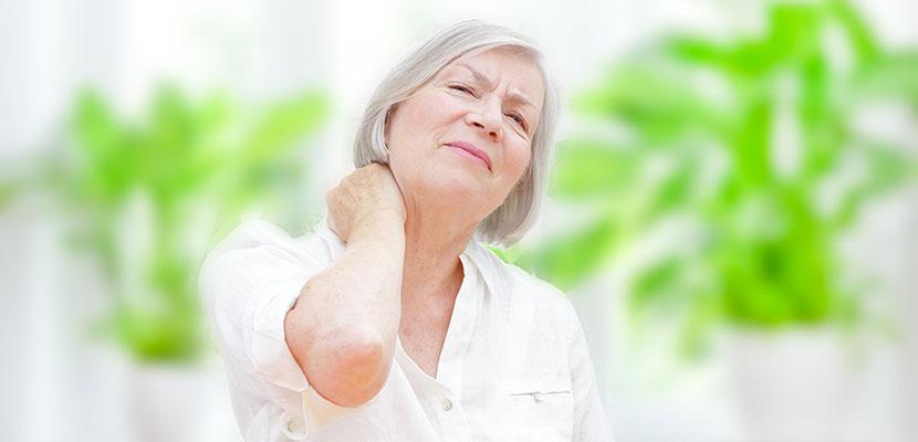 Frau greift sich auf den Nacken, weil sie Nackenschmerzen hat