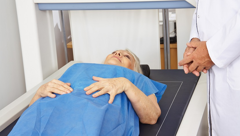 Seniorin liegt unter DXA zur Knochendichtemessung in der Radiologie