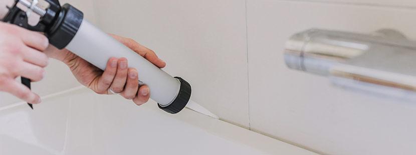 Eine Person zieht mit einer Presspistole Silikonfugen im Bad.