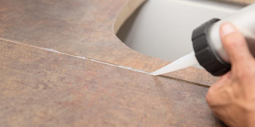 Eine Person zieht Silikonfugen zwischen Arbeitsplatten in der Küche.