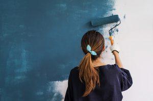 Wohnung streichen: Eine junge Frau streicht eine Wand mit blauer Farbe.