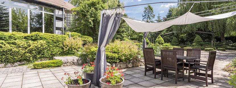 Terrassenplatten verlegen lassen: Ein Außenberei in dem Terrassenplatten aus Beton verlegt wurden. Darauf stehen Tisch und Stühle aus Holz.