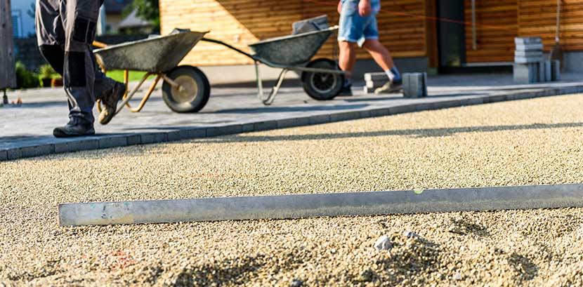 Terrassenplatten verlegen lassen: Zwei Personen verlegen Terrassenplatten auf Sand.