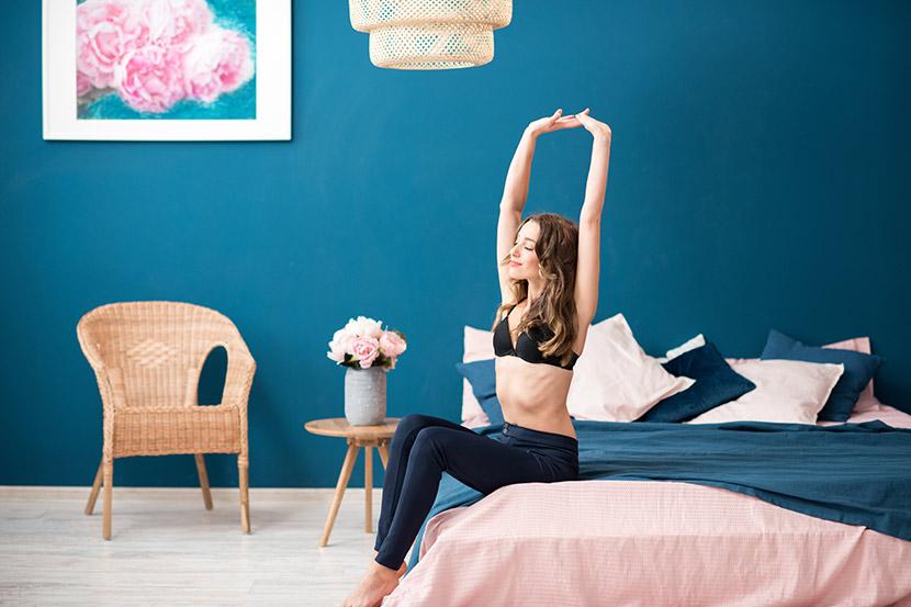 BH-Größen messen: eine junge Frau sitzt in Jeans und einem BH mit passender Körbchengröße auf ihrem Bett und streckt sich.
